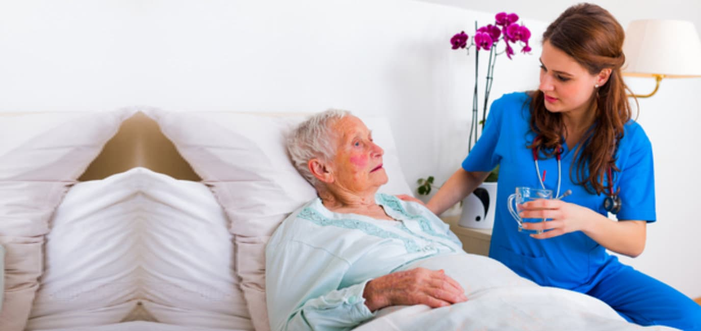 Kind geriatric doctor bringing water to senior woman in need