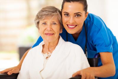 nurse and senior woman on wheelchair are smiling